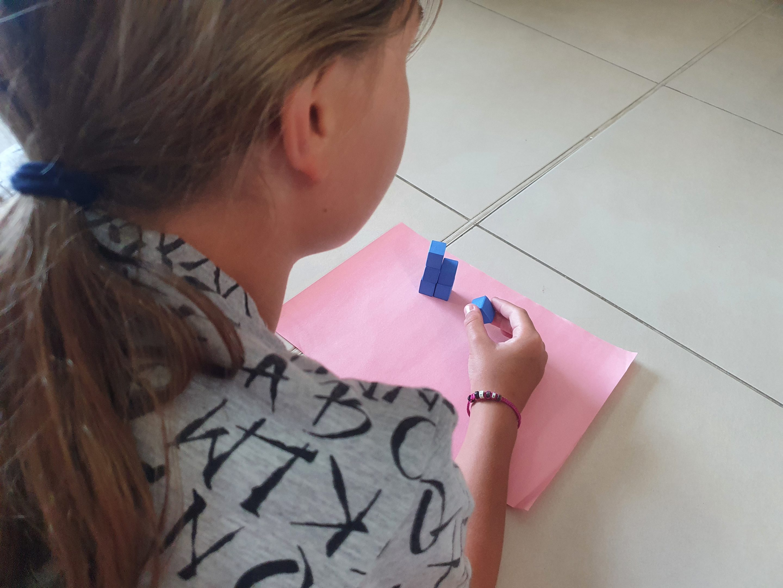 Kind liegt auf dem Boden und beschäftigt sich mit Mathe